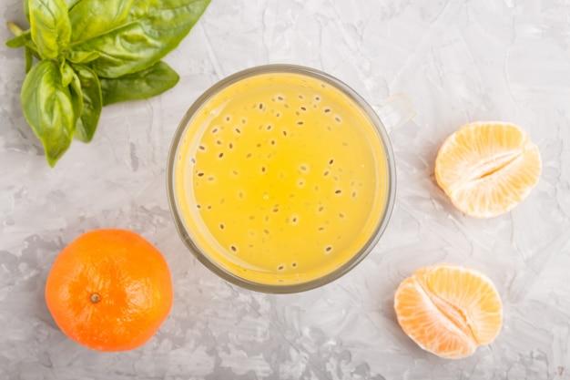 Copo de bebida colorida de laranja com tangerina com sementes de manjericão, sobre um fundo cinza de concreto