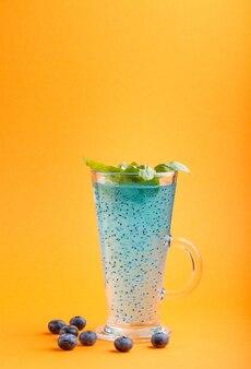Copo de bebida colorida de mirtilo azul com sementes de manjericão em fundo laranja