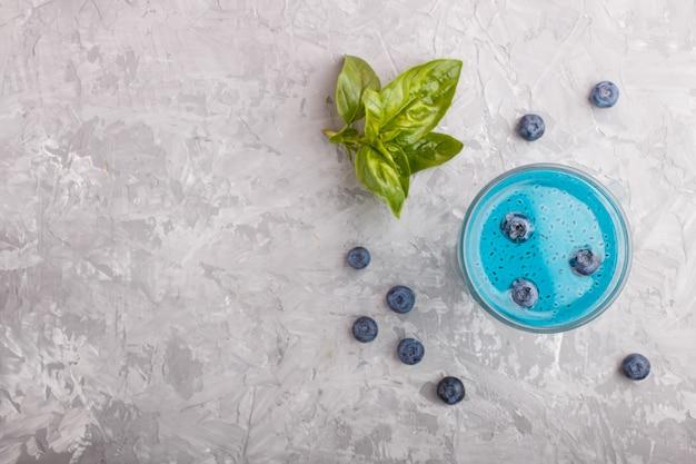 Copo de bebida colorida de mirtilo azul com sementes de manjericão, sobre um fundo cinza de concreto
