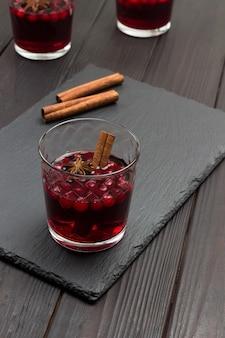 Copo de bebida com cranberries e especiarias. paus de canela na mesa. vista do topo