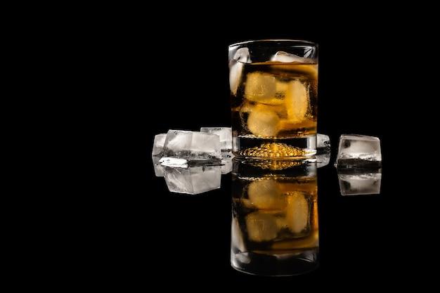 Copo de bebida com gelo na superfície refletida isolada