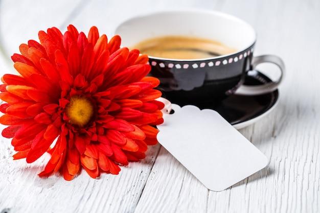 Copo de bebida de flores na mesa branca com cartão limpo