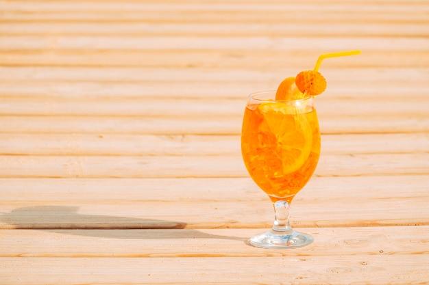 Copo de bebida de laranja apetitosa na superfície de madeira