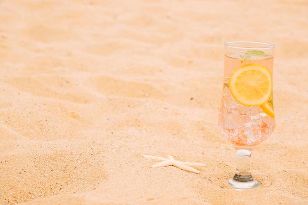 Copo de bebida gelada com fatias de frutas cítricas e estrelas do mar