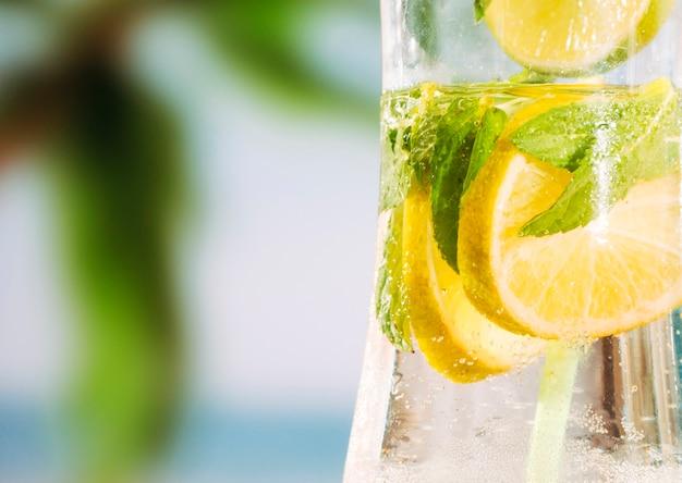 Copo de bebida gelada com limão fatiado e folhas de hortelã