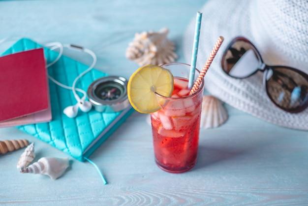 Copo de bebida limonada vermelha com limão e frutas e palha na mesa