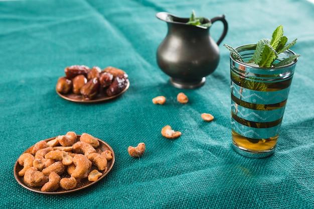Copo de bebida perto de jarro com plantas e frutos secos e nozes