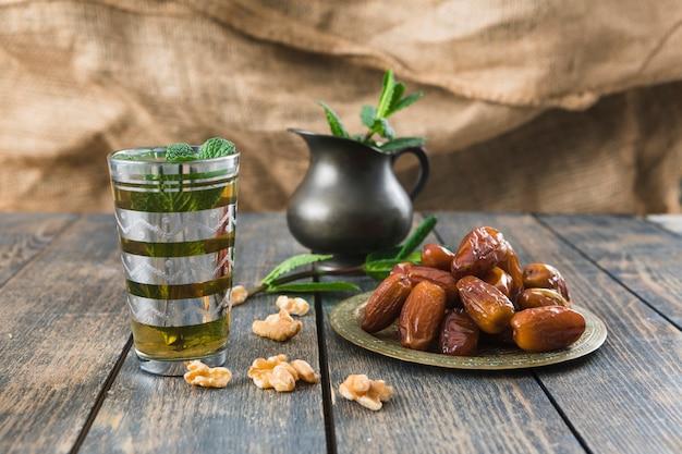 Copo de bebida perto de jarro, nozes, galhos de plantas e frutas secas na mesa