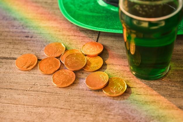 Copo de bebida perto de pilha de moedas e chapéu de saint patricks na mesa