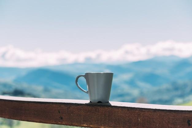 Copo de bebida quente colocado em uma cerca de madeira contra a incrível paisagem montanhosa em um dia ensolarado