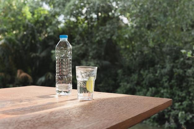 Copo de bebida refrescante de água com uma fatia de limão na mesa de madeira.