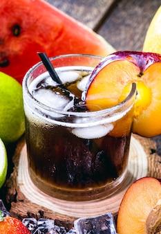 Copo de bebida típica brasileira chamada caipirinha, ameixa, álcool destilado, cachaça e açúcar. várias frutas ao redor