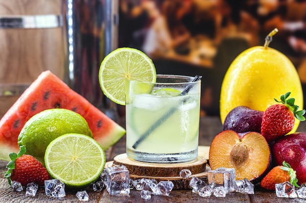 Copo de bebida típica brasileira chamada caipirinha, limão, álcool destilado, cachaça e açúcar. várias frutas ao redor