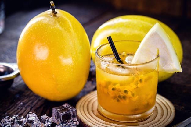 Copo de bebida típica brasileira chamada caipirinha, maracujá, álcool destilado, cachaça e açúcar. várias frutas ao redor