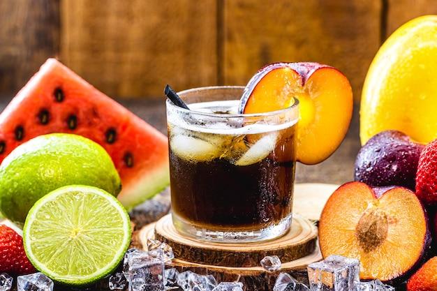 Copo de bebida típica brasileira chamada caipirinha, sabor ameixa, feita com frutas, álcool destilado e açúcar.