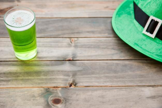 Copo de bebida verde e chapéu de saint patrick na mesa