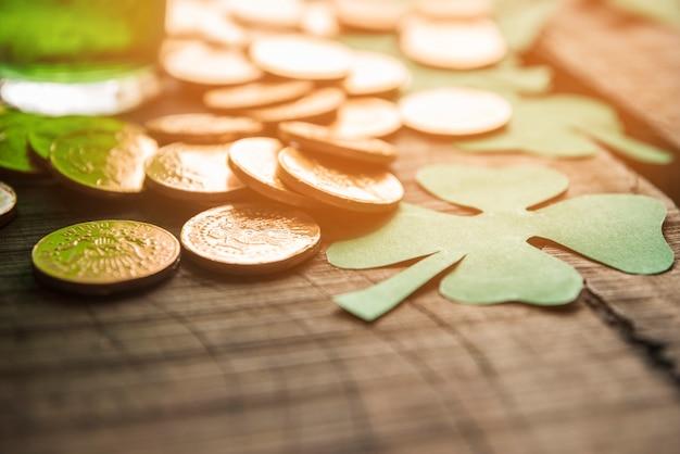Copo de bebida verde perto de pilha de moedas e trevos de papel na mesa
