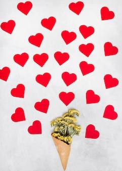 Copo de bolacha com flores perto de coleção de corações de ornamento