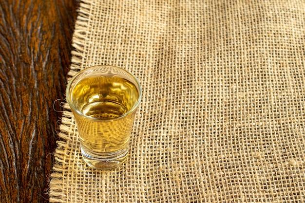 Copo de cachaça bebida típica brasileira em tecido de juta e mesa de madeira Foto Premium