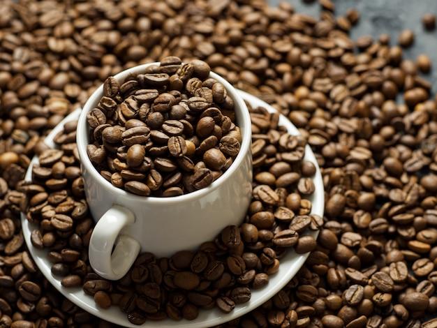 Copo de café branco cheio de grãos de café torrado de alta qualidade