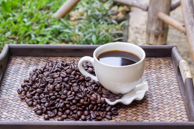 Copo de café branco com os feijões de café colocados em uma bandeja de madeira.