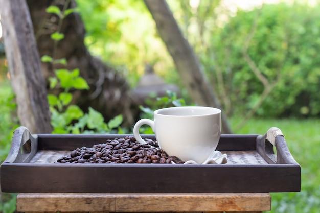 Copo de café branco com os feijões de café colocados em uma bandeja.