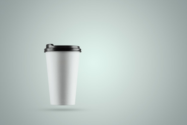 Copo de café branco de papel isolado em um fundo azul