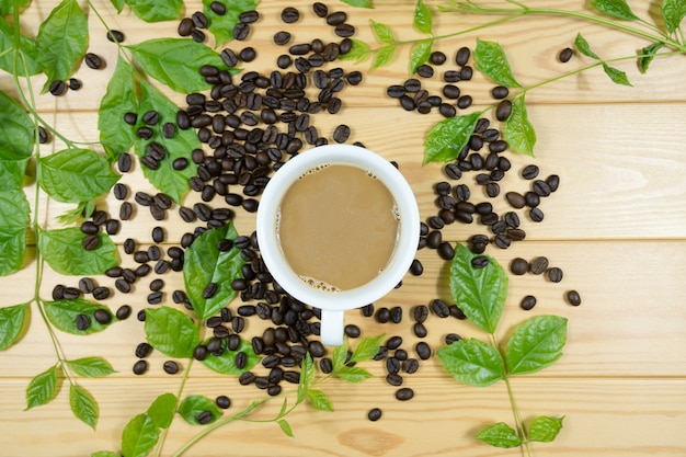 Copo de café branco, feijão e folhas verdes dos ramos no fundo de madeira.