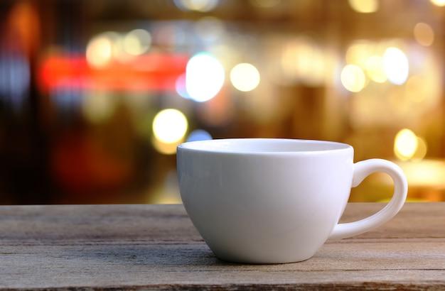 Copo de café branco na tabela de madeira no fundo do borrão da cafetaria.