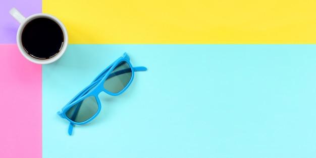Copo de café branco pequeno e óculos de sol azuis no fundo da textura do azul pastel da forma