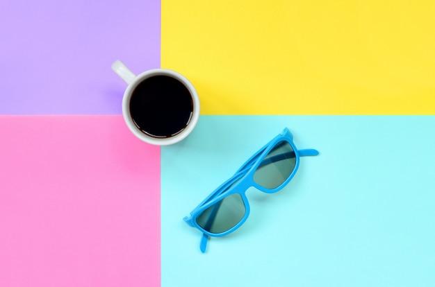 Copo de café branco pequeno e óculos de sol azuis no fundo da textura