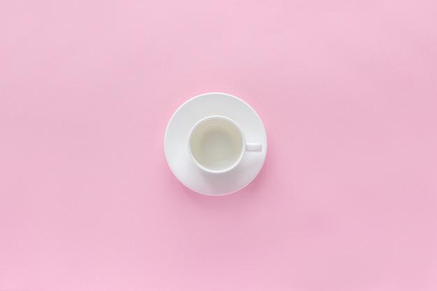 Copo de café branco vazio e prato pires no fundo rosa