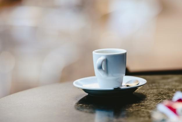Copo de café branco vazio na tabela de madeira de uma barra exterior, espaço negativo para o texto.