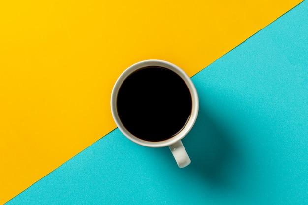 Copo de café cerâmico branco na mesa amarela e azul.