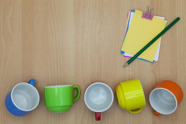 Copo de café colorido com nota de papel, lápis sobre fundo de madeira
