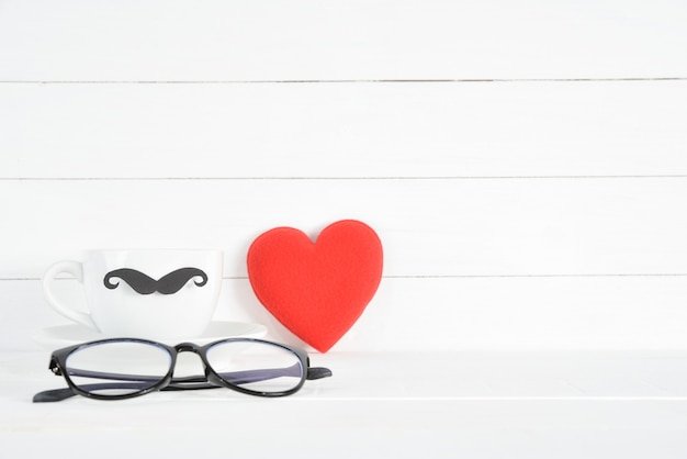 Copo de café com bigode de papel preto, óculos e coração vermelho em branco de madeira.