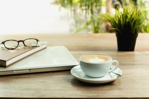 Copo de café com computador portátil e vidros na tabela de madeira.