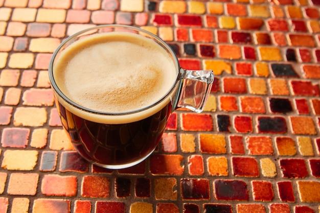 Copo de café com creme na mesa de azulejos vermelho