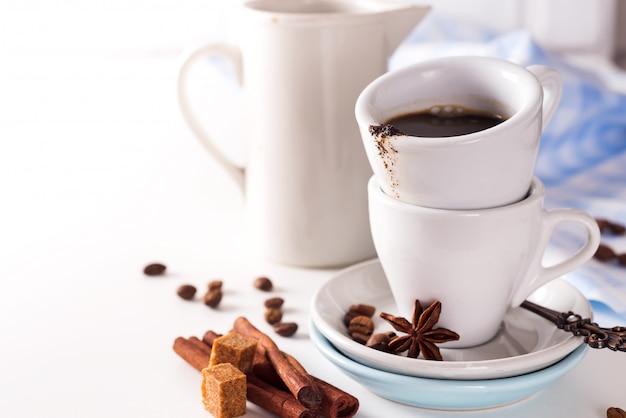 Copo de café com feijões de café e açúcar mascavado no fundo de pedra branco.