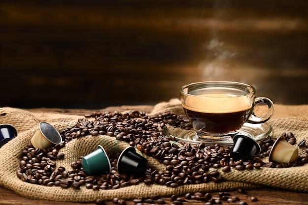 Copo de café com fumaça e grãos de café e cápsulas de café em saco de aniagem na velha mesa de madeira