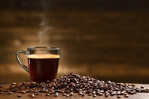 Copo de café com fumaça e grãos de café na velha mesa de madeira