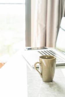 Copo de café com laptop e bela decoração de mesa de luxo no interior da sala para o fundo