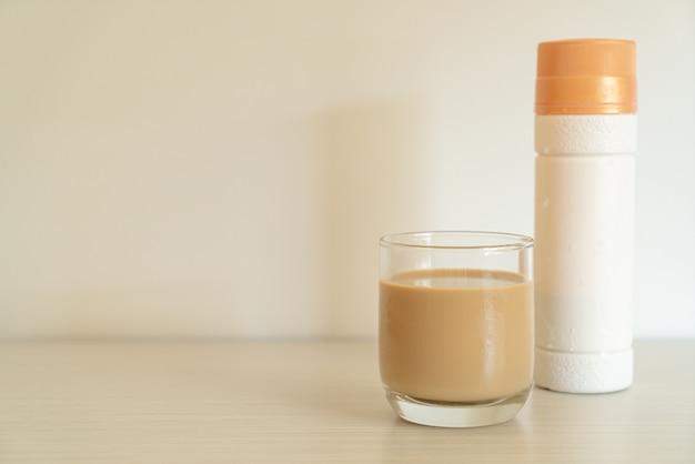 Copo de café com leite com garrafas de café prontas para beber na mesa