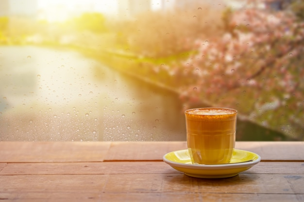 Copo de café com leite com latte art perto das janelas com queda de chuva depois da chuva pela manhã