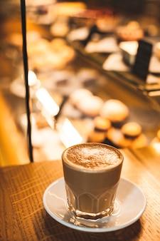 Copo de café com leite delicioso com fundo de item de padaria de desfocagem