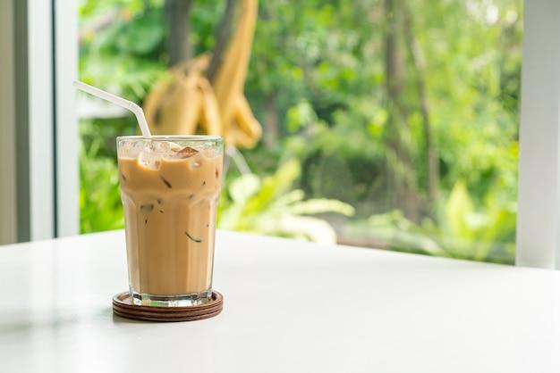 Copo de café com leite gelado na mesa de uma cafeteria