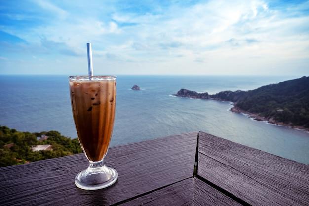 Copo de café com leite gelado no terraço da mesa de madeira com vista para o mar do pico da montanha