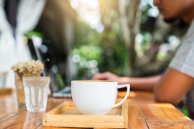 Copo de café da manhã na mesa com borrão homem trabalhando no computador portátil