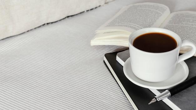 Copo de café de ângulo alto e livro