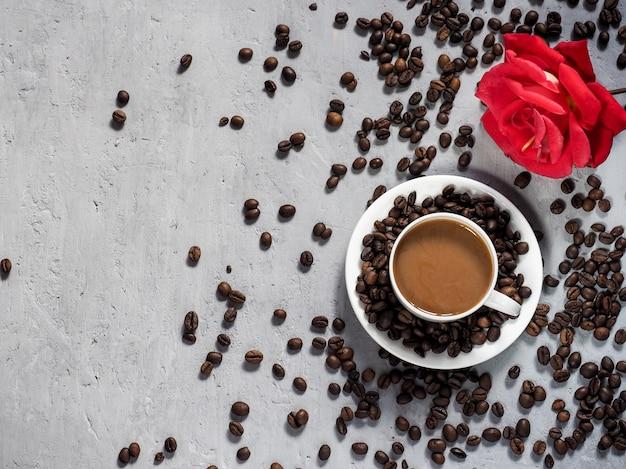 Copo de café de florescência da rosa do vermelho, feijões de café no fundo sob o concreto.